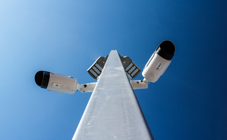 Two surveillance cameras on a pole with a blue background.