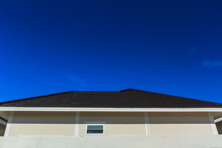 Dark brown tile roof on a blue background. Stock Photo
