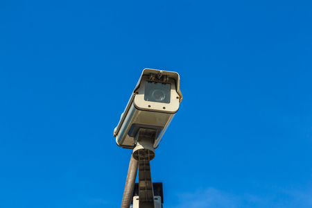 Security video camera on blue sky background.