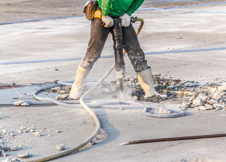worker of road construction drilling cement ground