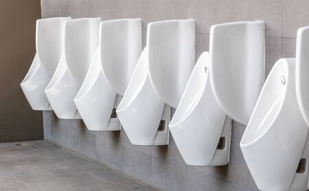 White urinal men with concrete wall in public toilet