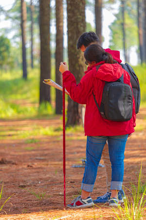 Men and women hiking with maps in the middle of nature