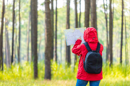 Woman traveler with backpack checks map to find directions Banque d'images
