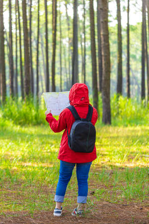 Women trekking alone with a map in the middle of nature