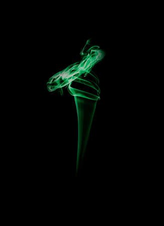 The smoke of incense stick are burning on the black background. Banque d'images