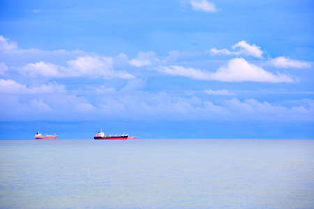 Long exposure shooting of small island boat and rock in smoky sea water with blue sky. Sky burst, blurred motion