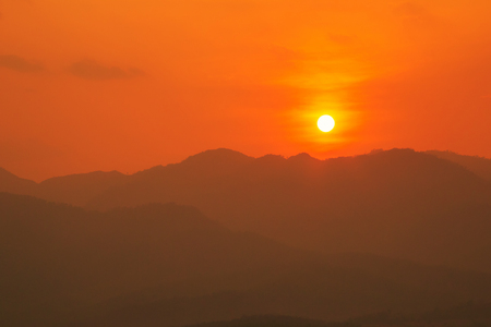 Red and orange warm sunlight in the sky during sunset with mountain  range in foreground, shade and shadow, sunset sunrise from Mae Hong Son province Thailand Stock Photo