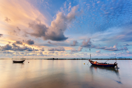 Fishing boat in perfectly calm sea water like glass with the clouds in the sky, long Exposure technic taken during sunrise