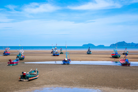 Many small fishing boats on sand beach during low tide with cloudy blue sky at Pranburi Prachuap-Kirikhan Thailand