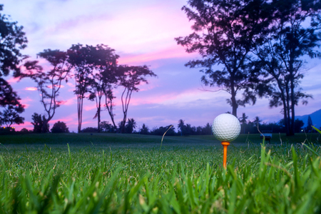 golf ball on tee at 1st hole tee off with blur green grass foreground and blur colorful sky with silhouette trees background during sunrise, Thailand