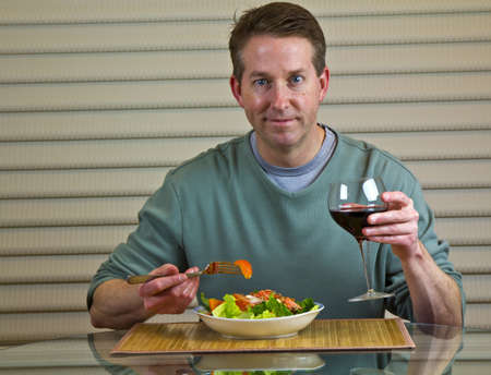 Mid-Aged Adult Men eating Red Salmon and Salad while drinking Merlot Stock Photo - 9014799
