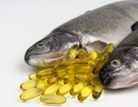 fish oil: Fresh Rainbow trout and fish oil capsules Stock Photo