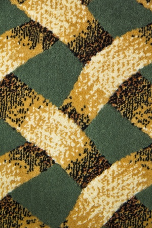 oriental rug: Texture of Rug with crossing patterns consiting of yellow, orange, green and white.  Stock Photo