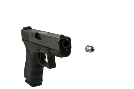 Black military pistol, inserted ammo clip and silver bullet being discharged photo