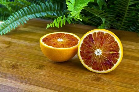 Cut Half of blood orange on bamboo counter photo