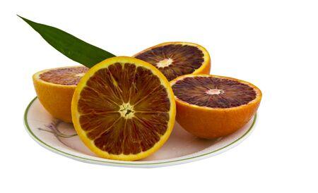 Fresh blood oranges cut in half on white dish photo
