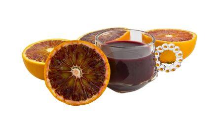 Freshly made blood orange surrounded by blood orange halves photo