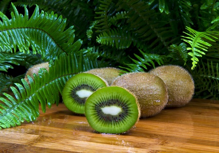 wholes: Ripe kiwi Fruit halves and wholes on bamboo setting with Ferns in background
