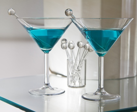 Dry mixed drinks on glass table with stir sticks photo