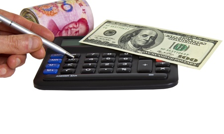 calculator chinese: Financial calculator, United States and Chinese currency, silver pen and hand Stock Photo