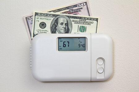 In deur set verwarmingsthermostaat bij een kamertemperatuur en geld Stockfoto