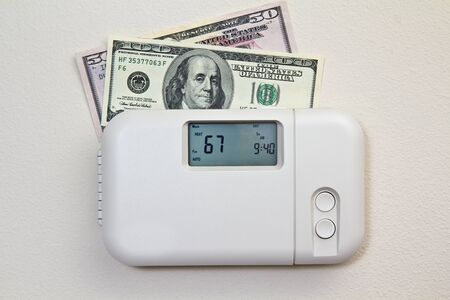 saving energy: In door heating thermostat set at a room temperature and money