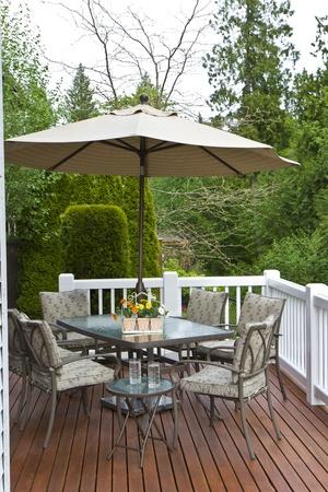 Cederhout terras, glazen tafel, stoelen, parasol en een drankje Stockfoto