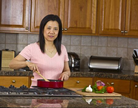 Asian women cooking in modern kitchen photo