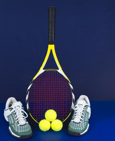 racquet: Tennis racket along with tennis shoes and balls on blue background