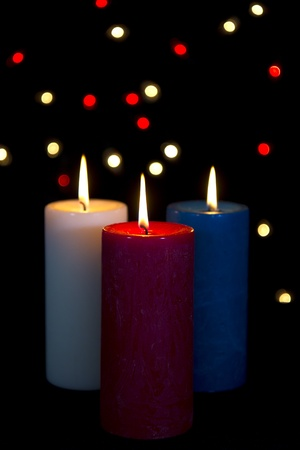 Colorful candles in white, red, blue on black background with lights photo