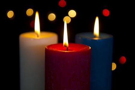 lighting background: Colorful candles in white, red, blue on black background with lights