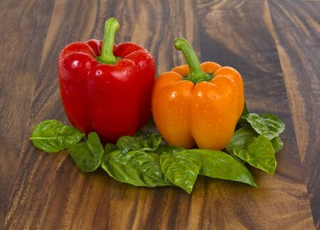 peper: Fresh basil and bell peppers on black walnut board Stock Photo