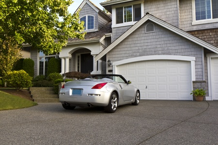 suburban home: Sporty car parked in front of home during summer Stock Photo