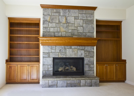 fireplace: Stone Fireplace with book shelves on white wall Stock Photo