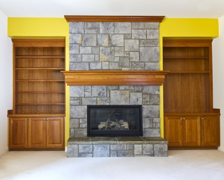 stone fireplace: Yellow Accent wall with fireplace and book shelves