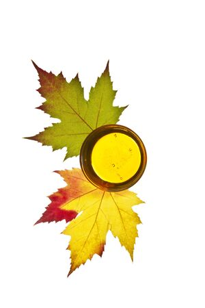 Pure golden maple syrup with colorful  maple leafs on white background
