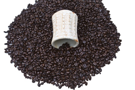 Freshly spilled coffee beans and mug on white background photo