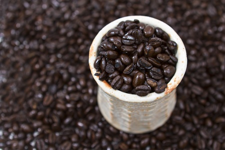 Coffee cup full of organic coffee beans