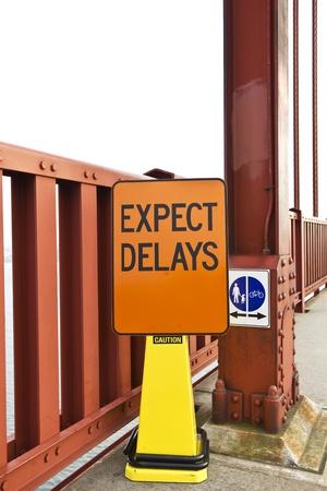 Orange traffic sign for delays on bridge construction