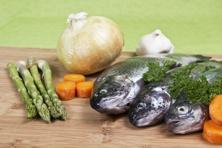 Fresh raw fish with parsley carrots garlic onion asparagus on bamboo board with green background Фото со стока