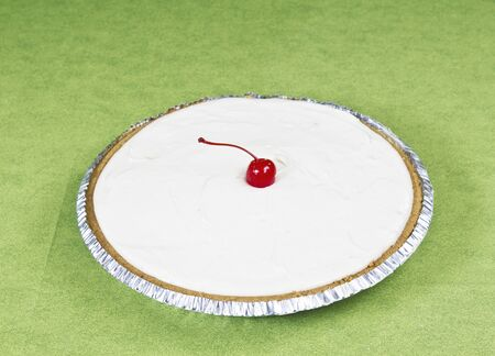 cream pie: Large cream pie with cherry in center on green background