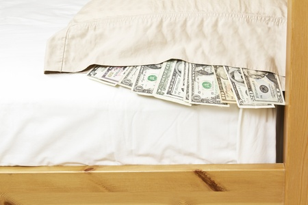 Paper currency underneath pillow case with bed frame and mattress as background photo