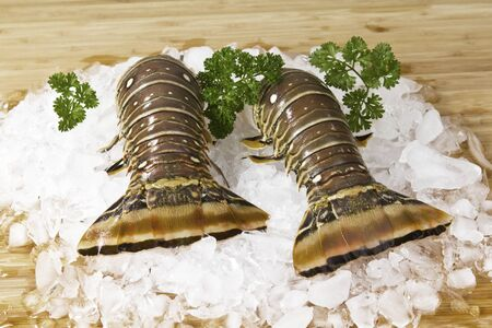Two lobster tails on ice with parsley and bamboo background