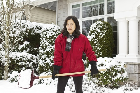 Women working outside cleaning snow in front of house photo