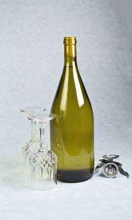 Light white wine in unopened bottle with two wine glasses and cork screw on blue table cloth