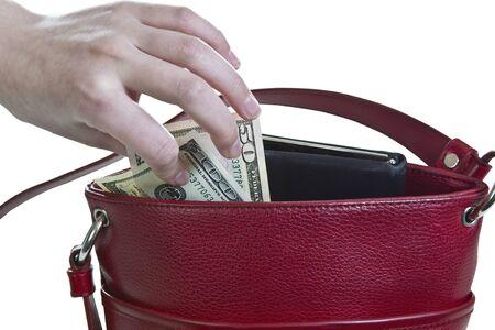 unconcerned: El dinero que se saca del bolso rojo sobre fondo blanco Foto de archivo