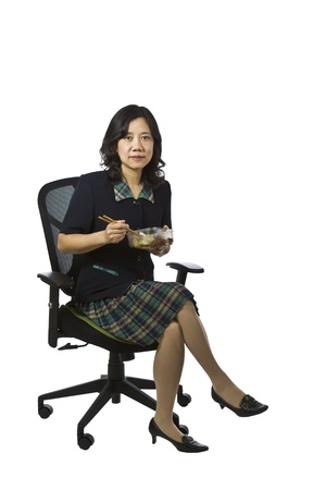 causal clothing: Asian women in business causal clothing holding lunch while sitting in chair on white background