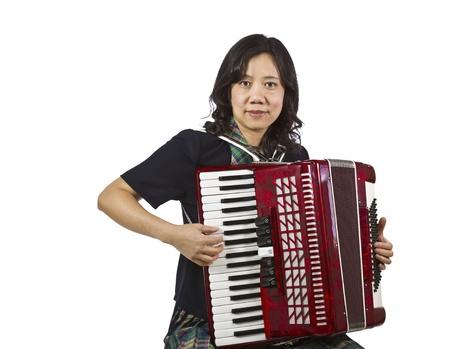 Asian women holding Accordion while sitting on white background photo
