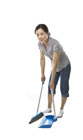 madre trabajando: Señora asiática con escoba y polvo sartén con ropa causal en el fondo blanco Foto de archivo