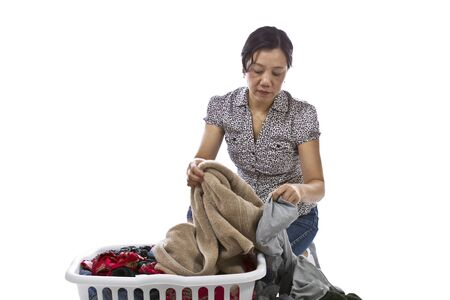 causal clothing: Asian lady sorting laundry in basket while wearing causal clothing on white background